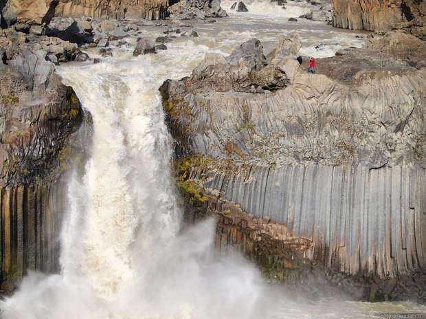 Aldeyjarfoss-waterfall-against-balast-columns-and-person-to-give-an-idea-of-its-size