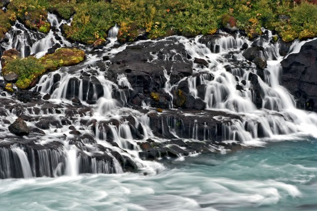 Close-up-of-Hraunfossar-which-means-lava-falls-and-the-blue-stream-that-the-waterfall-feeds-into